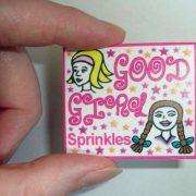 Hand holding a little envelope of good girl sprinkles.